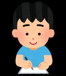 紙に文字を書いている男の子