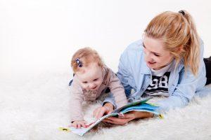 赤ちゃんがお母さんと一緒に絵本を読む