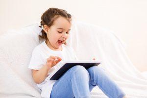 女の子がタブレットを使って楽しくオンライン勉強している