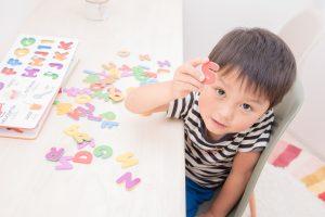子どもがアルファベットのパズルで遊んでいる