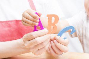 親子がアルファベットのおもちゃを一緒に持っている様子