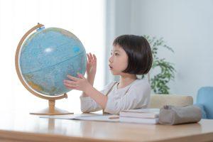 子どもが地球儀で遊んでいる様子